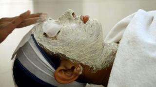 Una mujer india recibe un tratamiento facial en un salón de Nueva Delhi